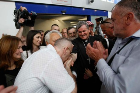 Dario Kordic kisses Bishop Vlado Kosic's hand Zagreb Airport 6 June 2014 (Photo: Ranko Suvar/CROPIX)