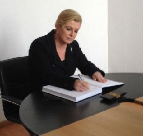 Croatia's President Kolinda Grabar-Kitarovic writing in the Book of Impressions at Jasenovac, 22 April 2015