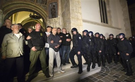 Supporters of Croatian war veterans guard the entry to St Mark's church Zagreb from armed riot police Photo: Darko Bandic/ AP Photo
