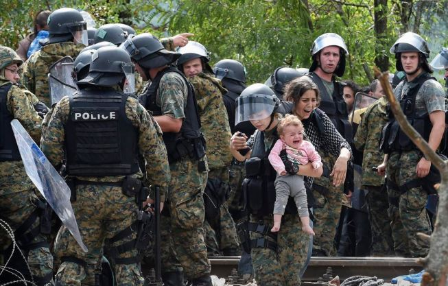 A member of the Macedonian special police forces holds a baby as migrants try to cross into Macedonia near the southern city of Gevgelija, The Former Yugoslav Republic of Macedonia, 22 August 2015 Photo: EPA/Georgi Licovski