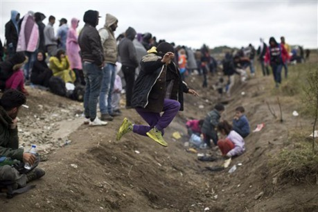A child jumps over a ditch as people wait in order to clear a police line after entering Croatia from Serbia in Strosinci, Croatia, Saturday, Sept. 26, 2015. Conciliation replaced confrontation among European nations which have clashed over their response to a wave of migration, but confusion faced many asylum-seekers streaming into Croatia on Saturday in hopes of chasing a new future in Western Europe. Photo: MARKO DROBNJAKOVIC — AP Photo