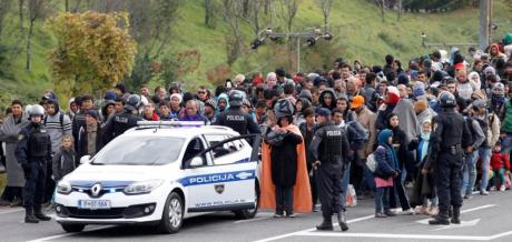 Slovenian policemen escort a group of migrants from a train towards a camp in Sentilj, Slovenia, Friday, Oct. 23, 2015. Thousands of people are trying to reach central and northern Europe via the Balkans but often have to wait for days in mud and rain at the Serbian, Croatian and Slovenian borders. (AP Photo/Petr David Josek)