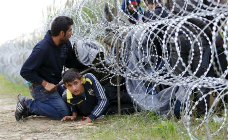 Syrian migrants breaking through razor-wire fencing Hungary/Croatia border