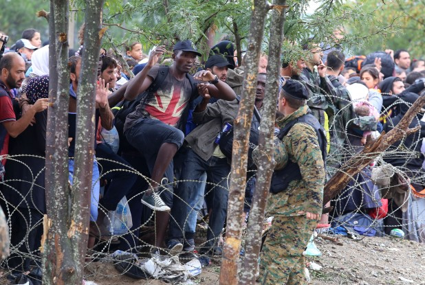 Migrants break the police blockade to enter into Macedonia from Greece late 2015 (AP Photo/Vlatko Perkovski)